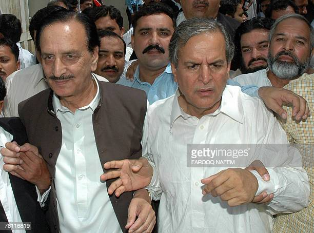 Raja Zafar ulHaq and Javed Hashmi senior party leaders of exiled former Pakistani Prime Minister Nawaz Sharif leave the supreme court building with...