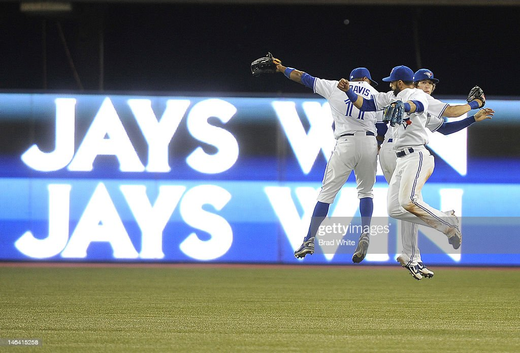 Rajai Davis #11, Colby Rasmus #28 and Jose Bautista #19 of the Toronto Blue Jays celebrate a win over the Philadelphia Phillies during interleague MLB game action June 15, 2012 at Rogers Centre in Toronto, Ontario, Canada.