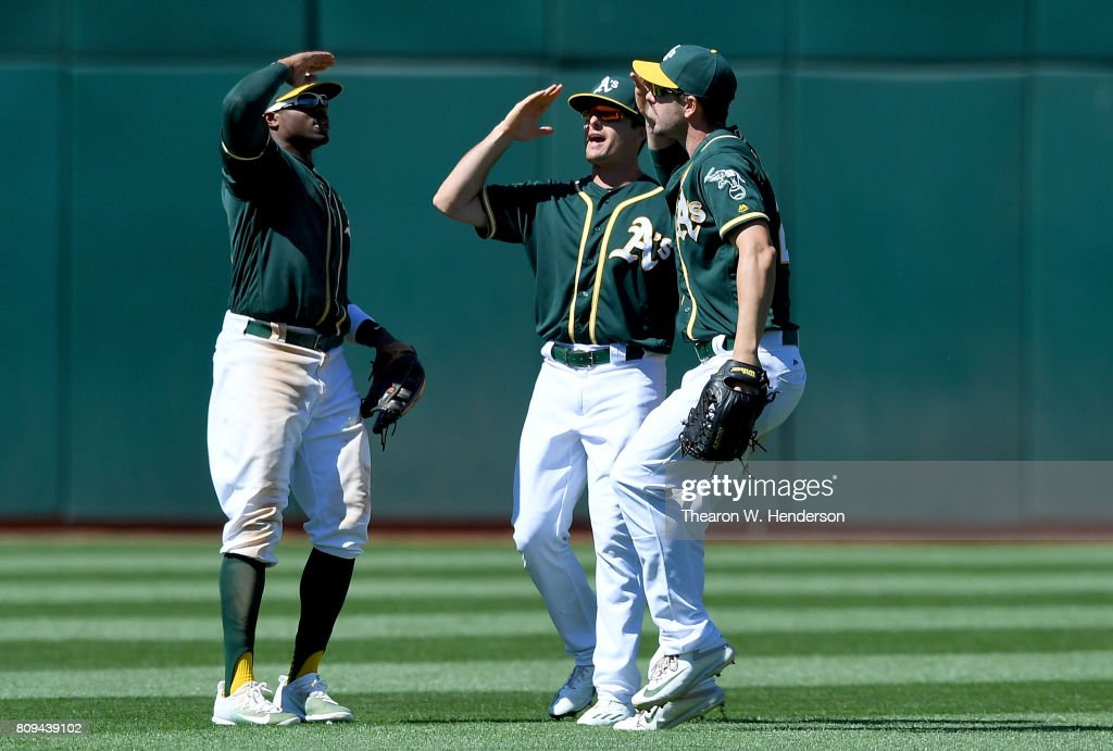 Rajai Davis #11, Jaycob Brugman #38 and Matt Joyce #23 of the Oakland Athletics celebrates defeating the Chicago White Sox 7-4 at Oakland Alameda Coliseum on July 5, 2017 in Oakland, California.