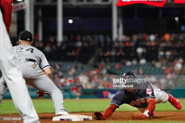 Rajai Davis of the Cleveland Indians dives back to first base ahead of the tag by Matt Davidson of the Chicago White Sox on a pickoff attempt in the...