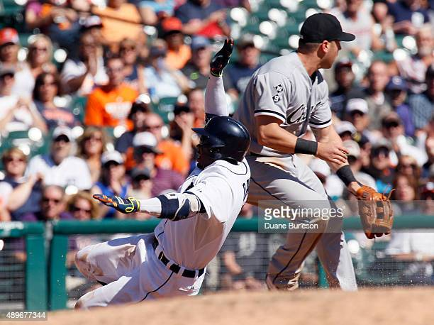 Rajai Davis of the Detroit Tigers slides into third base past Mike Olt of the Chicago White Sox for a triple during the fourth inning at Comerica...