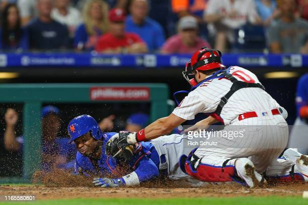 Rajai Davis of the New York Mets is tagged out by catcher J.T. Realmuto of the Philadelphia Phillies as he attempted to score on a fielder's choice...