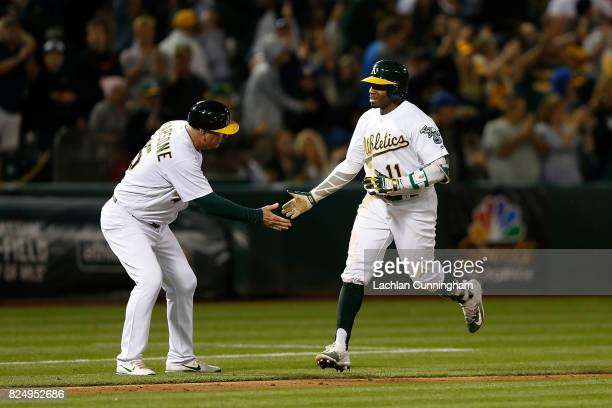 Rajai Davis of the Oakland Athletics celebrates with third base coach Steve Scarsone after hitting a tworun walkoff home run in the ninth inning...