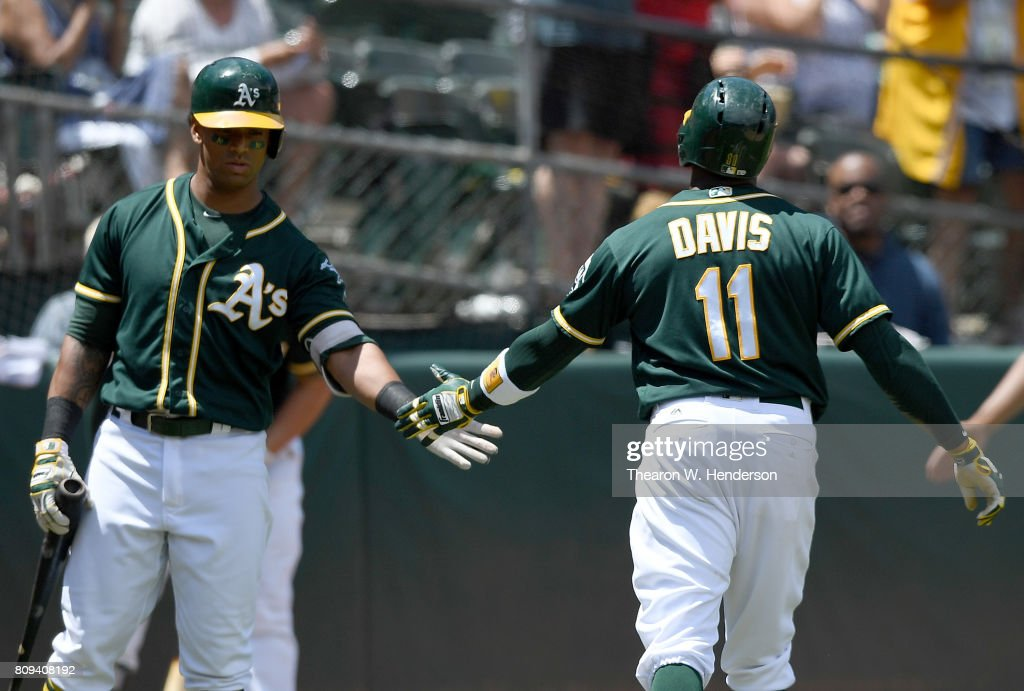 Rajai Davis #11 of the Oakland Athletics is congratulated by Khris Davis #2 after Rajai scored against the Chicago White Sox in the bottom of the fourth inning at Oakland Alameda Coliseum on July 5, 2017 in Oakland, California.