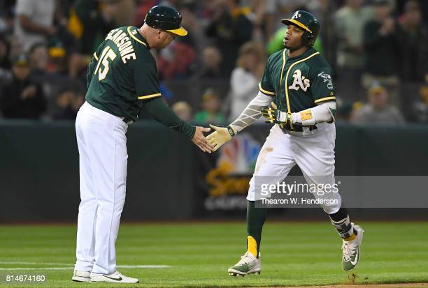 Rajai Davis of the Oakland Athletics is congratulated by third base coach Steve Scarsone after Davis hit solo home run against the Cleveland Indians...