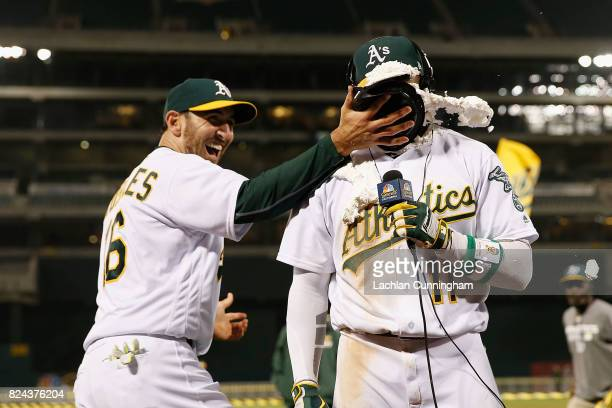 Rajai Davis of the Oakland Athletics is hit with a pie by teammate Adam Rosales of the Oakland Athletics after Davis hit a tworun walkoff home run in...