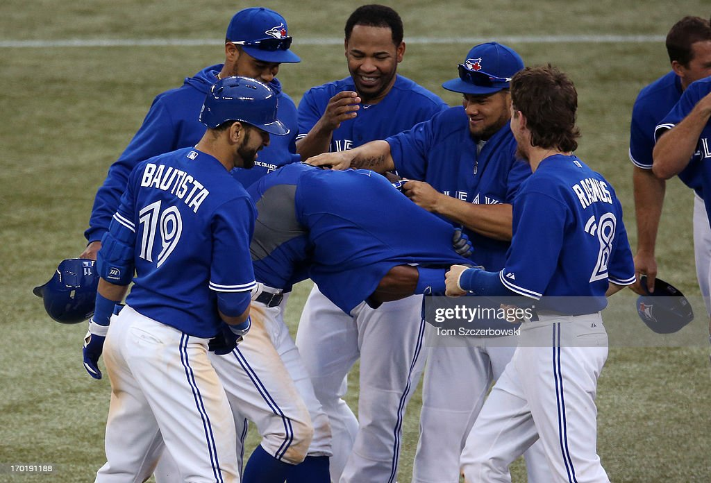 Rajai Davis #11 of the Toronto Blue Jays is embraced by teammates after driving in the winning run in the eighteenth inning during MLB game action against the Texas Rangers on June 8, 2013 at Rogers Centre in Toronto, Ontario, Canada.