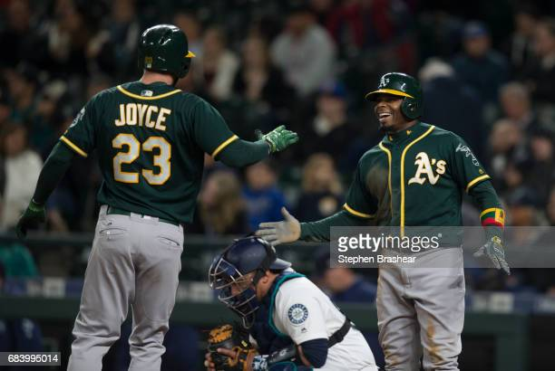 Rajai Davis right of the Oakland Athletics congratulates Matt Joyce of the Oakland Athletics in front of catcher Carlos Ruiz of the Seattle Mariners...