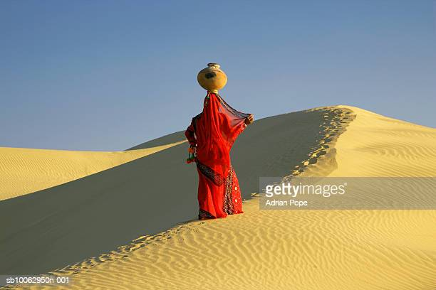 Rajastani woman in traditional costume carrying water jug on sand dunes
