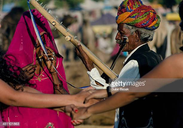 Rajastani woman singing traditional songs while her husband is playing music with traditional wooden stringed instrument on November 25,2012 in...