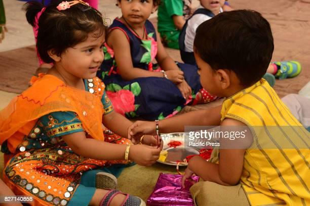 Rajasthani children tie 'rakhi' on the wrist of a male classmate in celebration of Raksha Bandhan in India