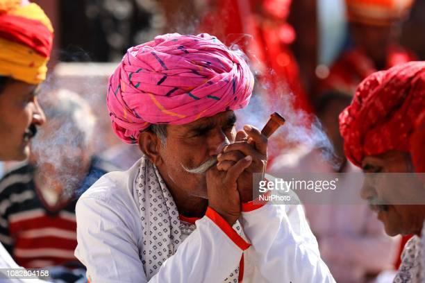 Rajasthani folk artists smoke during Kite Festival on the occasion of Makar Sankranti at Jal Mahal in Jaipur,Rajasthan,India ,Jan 14,2019.