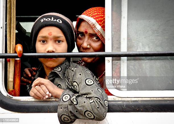 CONTENT] Rajasthani mother and son looking out of a bus window in Pushkar Rajasthan India