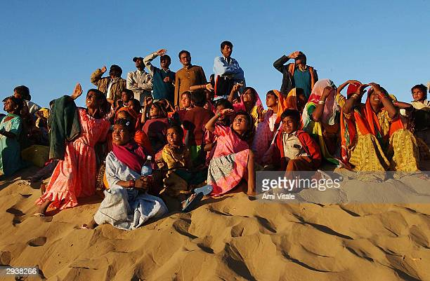 Rajasthani tourists watch Indian paratroopers jump out of a helicopter on the last day of the Desert Festival of Jaisalmer on February 6 2004 in...