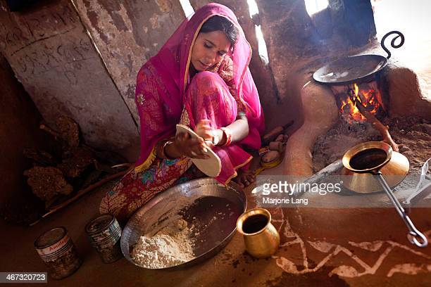 Rajasthani woman cooking chapatis in her traditional kitchen with tawa and other ustensils. In the countryside around Jodhpur, Rajasthan, India.