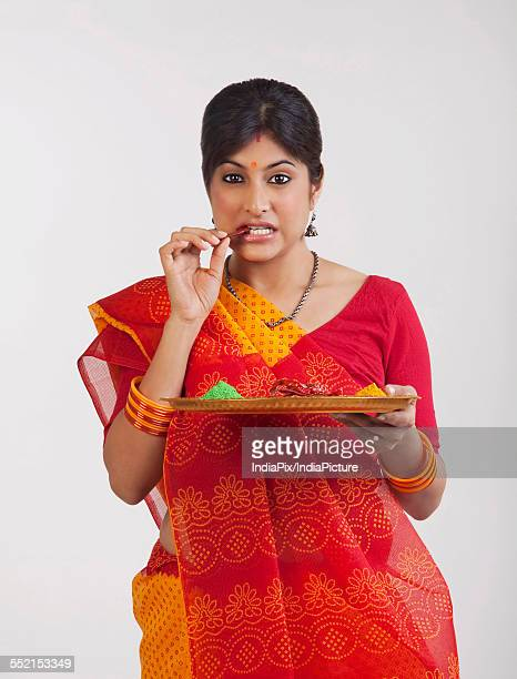 A Rajasthani woman eating a red chilli