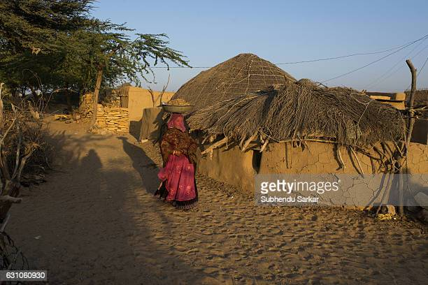 Rajasthani woman in traditional dress carries load on her head in a village