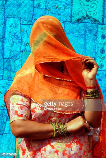 rajasthani woman in veil standing against blue bedsheet, jaisalmer, rajasthan, india - dupatta stock pictures, royalty-free photos & images