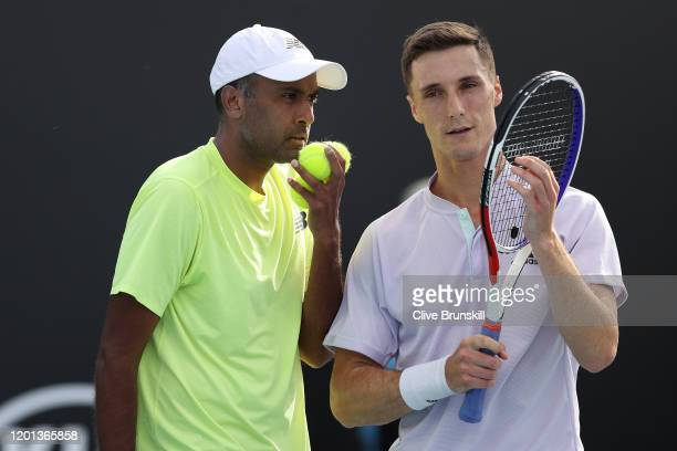 Rajeev Ram of the United States and Joe Salisbury of Great Britain talk tactics during their Men's Doubles first round match against Daniel Evans of...