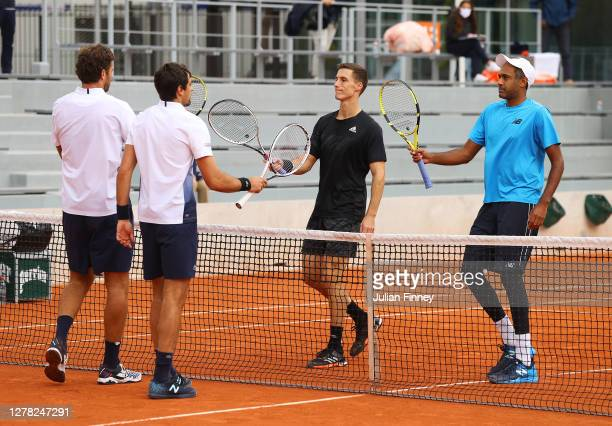 Rajeev Ram of The United States of America and Joe Salisbury of Great Britain knock racquets at the net with Jeremy Chardy and Fabrice Martin of...