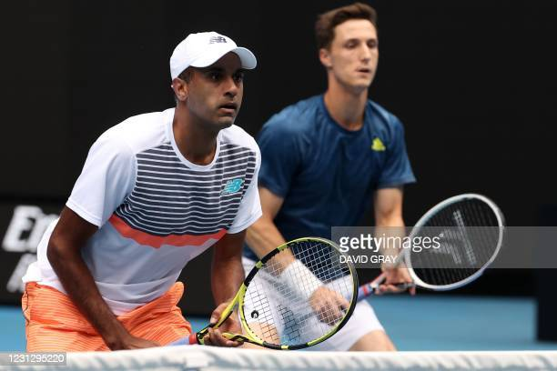 Rajeev Ram of the US and partner Britain's Joe Salisbury wait to hit a return during their men's doubles final match against Croatia's Ivan Dodig and...