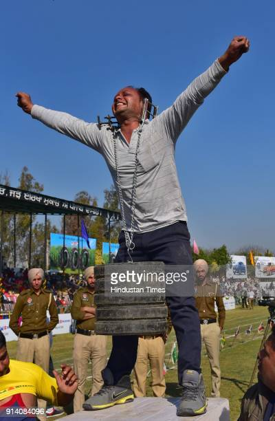 Rajinder Kumar showing the strength by lifting 88kg weight with his ears on the 2nd day of the 82nd Kila Raipur Rural Olympics 2018 in the village...