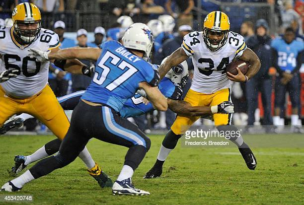 Rajion Neal of the Green Bay Packers carries the ball against Patrick Bailey of the Tennessee Titans at LP Field on August 9 2014 in Nashville...