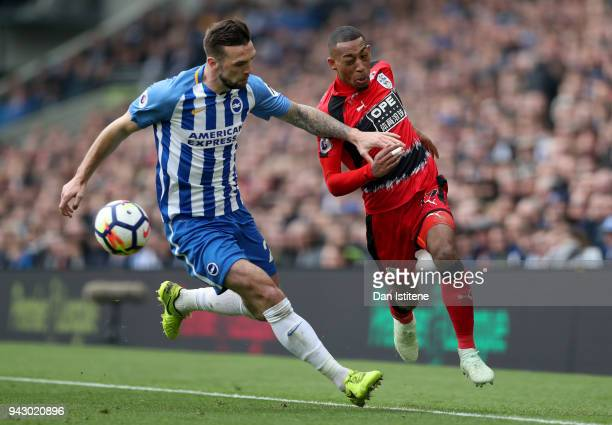 Rajiv van La Parra of Huddersfield Town and Shane Duffy of Brighton and Hove Albion battle for the ball during the Premier League match between...