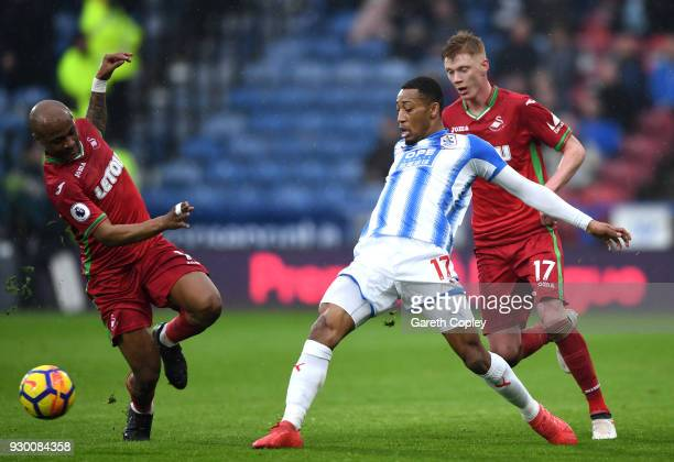 Rajiv van La Parra of Huddersfield Town is challenged by Andre Ayew of Swansea City and Samuel Clucas of Swansea City during the Premier League match...