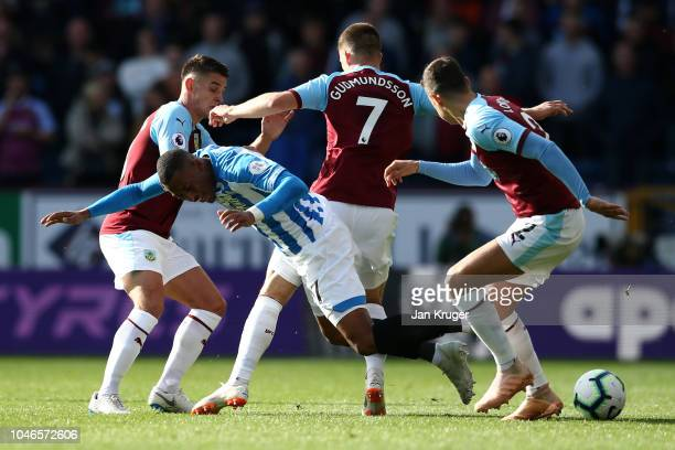 Rajiv van La Parra of Huddersfield Town is challenged by Johann Gudmundsson of Burnley and Matthew Lowton of Burnley during the Premier League match...