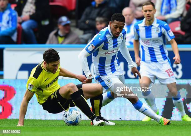 Rajiv Van La Parra of Huddersfield Town is tackled by John Mousinho of Burton Albion during the Sky Bet Championship match between Huddersfield Town...