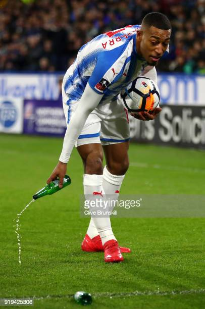 Rajiv van La Parra of Huddersfield Town removes bottles thrown onto the pitch during the The Emirates FA Cup Fifth Round between Huddersfield Town v...