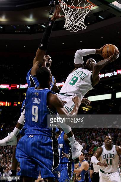 Rajon Rondo of the Boston Celtics attempts a shot as he falls and was fouled against Dwight Howard of the Orlando Magic in Game Six of the Eastern...