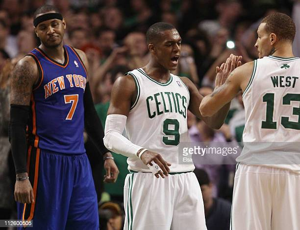 Rajon Rondo of the Boston Celtics congratulates Delonte West after he made a free throw with 6 seconds left in the game as Carmelo Anthony of the New...