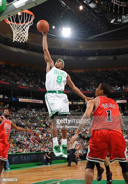 Rajon Rondo of the Boston Celtics dunks the ball against Derrick Rose of the Chicago Bulls in Game Five of the Eastern Conference Quarterfinals...