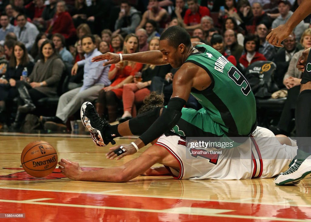 Rajon Rondo #9 of the Boston Celtics lands on top of Joakim Noah #13 of the Chicago Bulls as they battle for a loose ball at the United Center on December 18, 2012 in Chicago, Illinois. The Bulls defeated the Celtics 100-89.