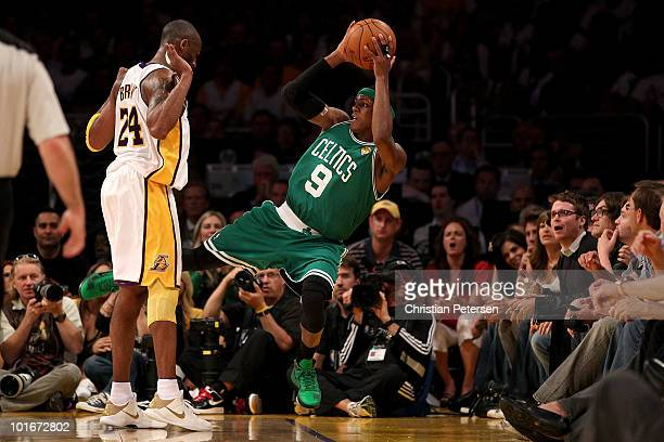 Rajon Rondo of the Boston Celtics tries to save the ball from going out of bounds while under pressure from Kobe Bryant of the Los Angeles Lakers in...