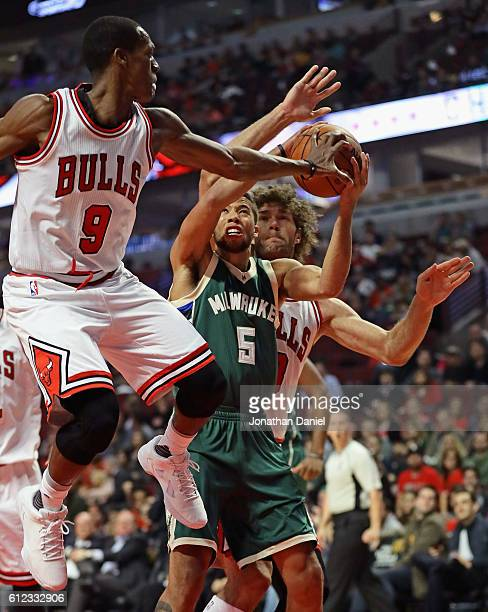Rajon Rondo of the Chicago Bulls gets his hand on the ball as Michael CarterWilliams of the Milwaukee Bucks tries to shoot during a preseason game at...