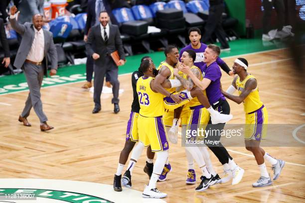Rajon Rondo of the Los Angeles Lakers center celebrates with LeBron James and Kyle Kuzma after scoring the game winning basket against the Boston...
