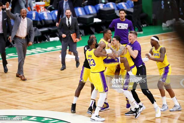 Rajon Rondo of the Los Angeles Lakers center is picked up by LeBron James and Kyle Kuzma after scoring the game winning basket against the Boston...