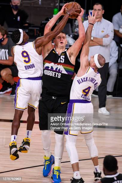 Rajon Rondo of the Los Angeles Lakers fouls Nikola Jokic of the Denver Nuggets as Alex Caruso helps defend during the fourth quarter of Denver's...