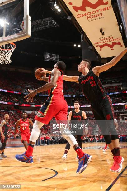 Rajon Rondo of the New Orleans Pelicans and Zach Collins of the Portland Trail Blazers reach for the ball during the game btween the two teams in...