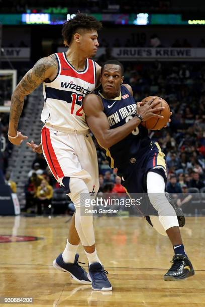 Rajon Rondo of the New Orleans Pelicans dribbles past Kelly Oubre Jr #12 of the Washington Wizards during the first half of a NBA game at Smoothie...