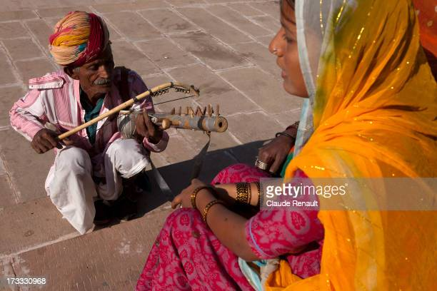 Rajuri singing traditionnal songs while Rampal, her uncle, is playing music on the Ghats in Pushkar. Rajasthan.