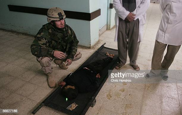 Rakan Hassan lies paralyzed on a stretcher while a US medic kneels over him after being accidentally shot by US soldiers January 18 2005 in Tal Afar...