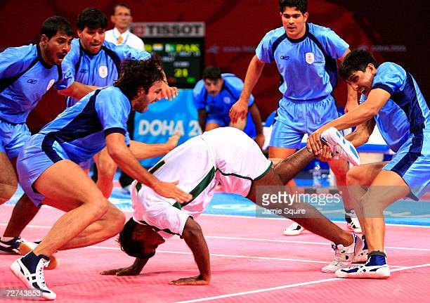 Rakesh Kumar of Pakistan is taken down from the India team in the Men's Kabaddi Gold Medal match at the 15th Asian Games Doha 2006 at Aspire Hall on...
