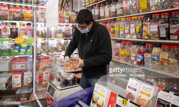 Rakesh Parmer weighs out sweets at Ye Olde Sweet Shoppe in Leicester as the city may be the first UK location to be subjected to a local lockdown...