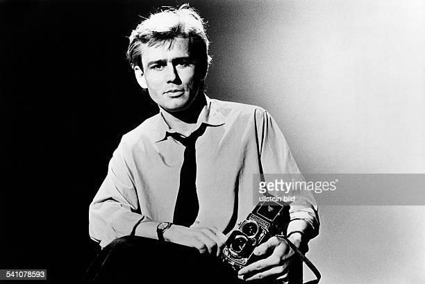 Rakete Jim *Fotograf Fotojournalist D Halbportrait haelt eine Fotokamera im Arm 1983