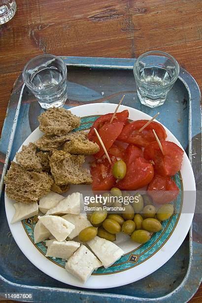 Raki or tsikoudia accompanied with olives rusks goat cheese and tomatos another typical Cretan traditional snack on August 08 2010 in Heraklion Greece