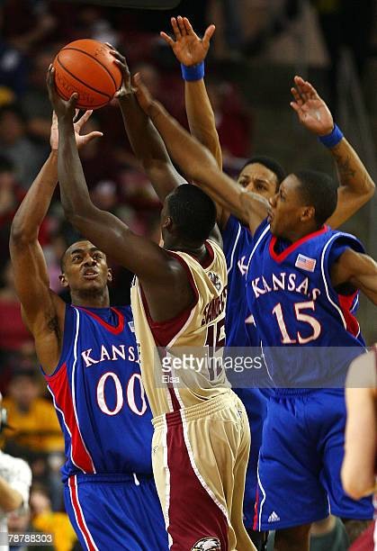 Rakim Sanders of the Boston College Eagles tries to take a shot as he is surrounded by Darrell Arthur Mario Chalmers and Brandon Rush of the Kansas...